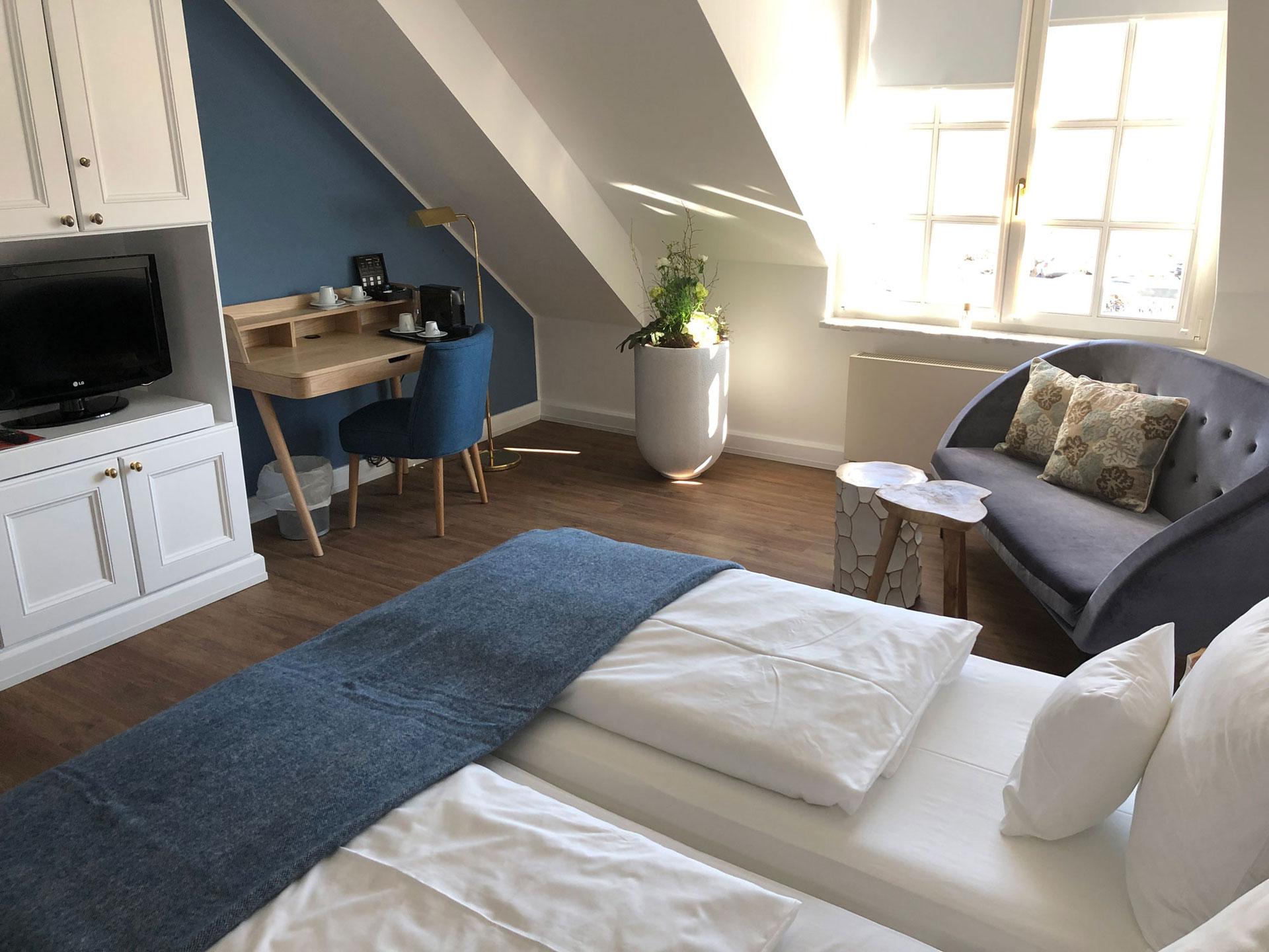 Einblick in das Doppelzimmer De Luxe mit Sitznische, Schreibtisch und Flatscreen TV im Hofgut Georgenthal