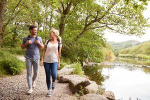 Ein sich anlächelndes Pärchen beim Wandern in der idyllischen Natur des Taunus