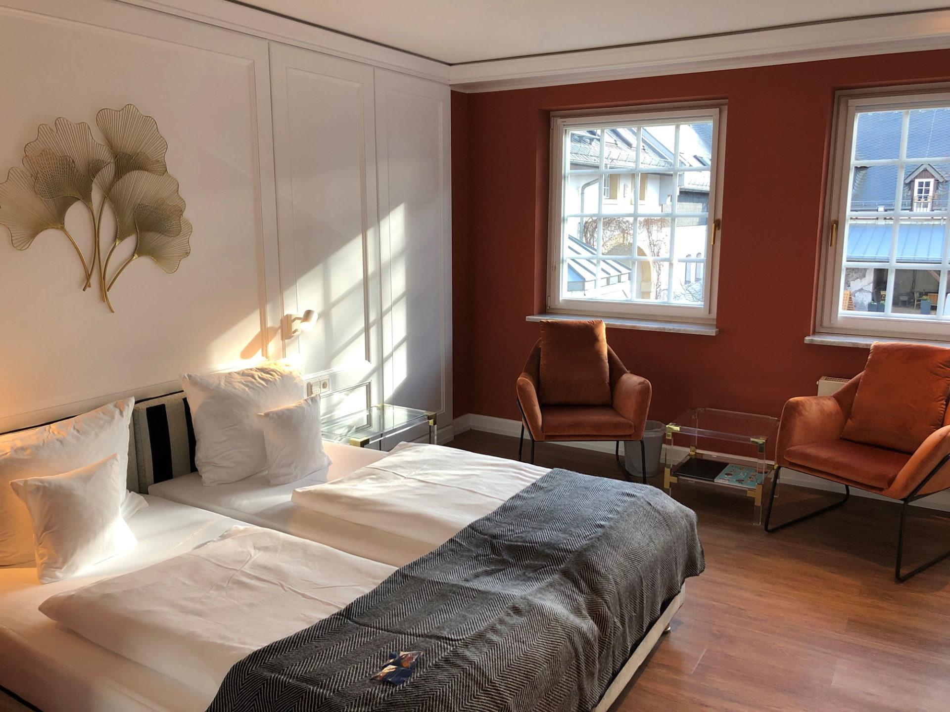 Einblick in das Komfort Doppelzimmer mit zusätzlichen Sitzmöglichkeiten neben dem Doppelbett im Hofgut Georgenthal