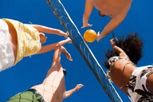 Vier Personen beim Beachvolleyball spielen